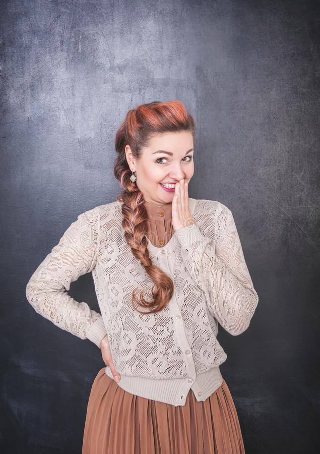 Όμορφη γυναίκα giggle στο υπόβαθρο πινάκων στοκ φωτογραφία