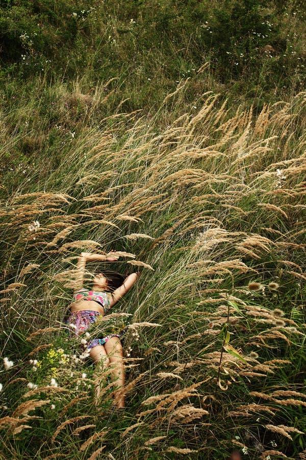 Όμορφη γυναίκα hipster που βρίσκεται στη χλόη στο θερινό λιβάδι και πραγματική στοκ φωτογραφίες με δικαίωμα ελεύθερης χρήσης