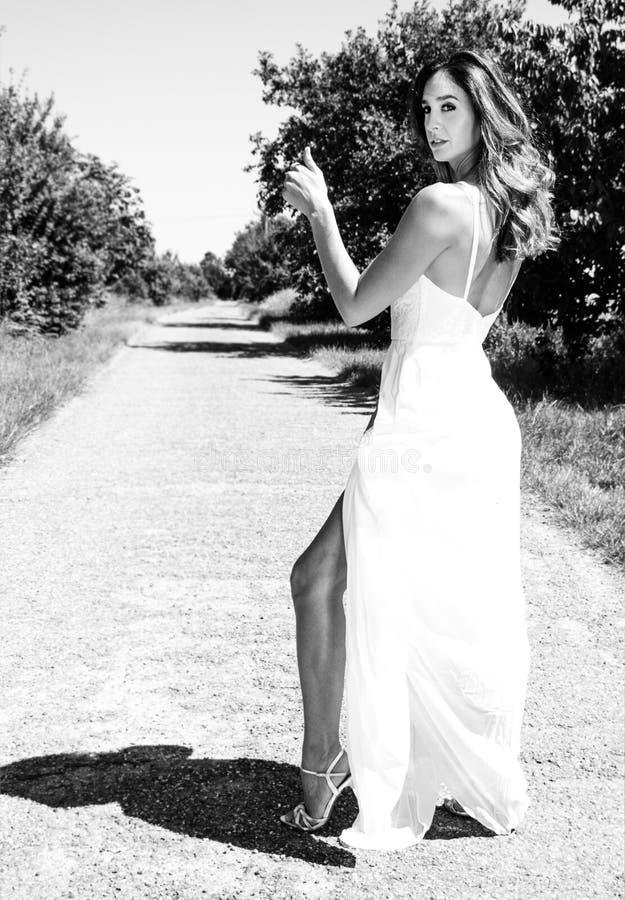 Όμορφη γυναίκα, hitchhiker νυφών στους άσπρους αντίχειρες φορεμάτων για έναν ανελκυστήρα σε μια εθνική οδό παρουσιάζοντας πόδι τη στοκ εικόνα με δικαίωμα ελεύθερης χρήσης