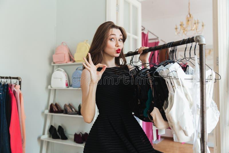 Όμορφη γυναίκα shopaholic στο φόρεμα που στέκεται στο ράφι ενδυμάτων στοκ φωτογραφία