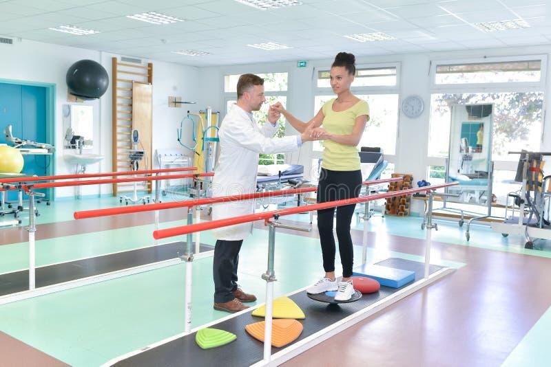 Όμορφη γυναίκα treadmill στην αποκατάσταση που ενισχύεται από το θεράποντα στοκ φωτογραφία με δικαίωμα ελεύθερης χρήσης