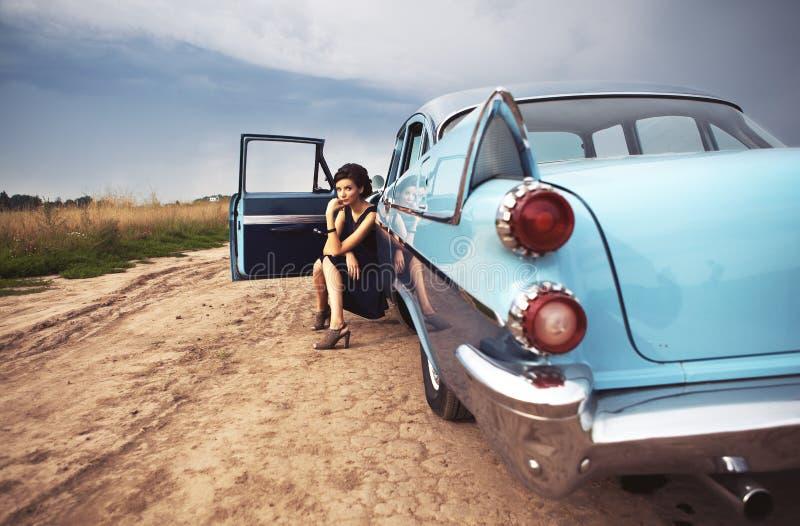 Όμορφη γυναικεία συνεδρίαση σε ένα αναδρομικό αυτοκίνητο στοκ φωτογραφίες