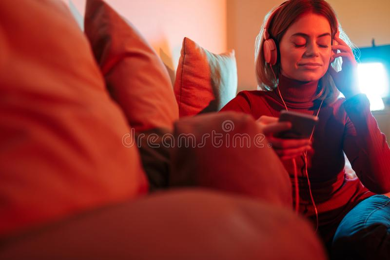 Όμορφη γυναικεία συνεδρίαση στον καναπέ και ονειρεμένα κλείσιμο της μουσικής ακούσματος ματιών της στα ακουστικά στο σπίτι στοκ φωτογραφία με δικαίωμα ελεύθερης χρήσης