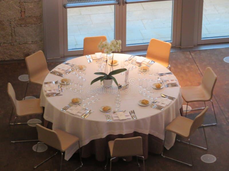 Όμορφη διάσκεψη στρογγυλής τραπέζης έτοιμη να λάβει τους φιλοξενουμένους και να πάρει να φάει στοκ εικόνα