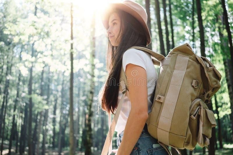 Όμορφη διακινούμενη γυναίκα με το σακίδιο πλάτης και καπέλο που στέκεται στο δασικό νέο περπάτημα κοριτσιών hipster μεταξύ των δέ στοκ φωτογραφία