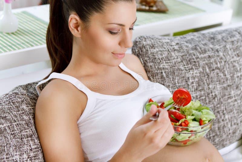 Όμορφη εγκυμοσύνη που τρώει τη σαλάτα στοκ εικόνες