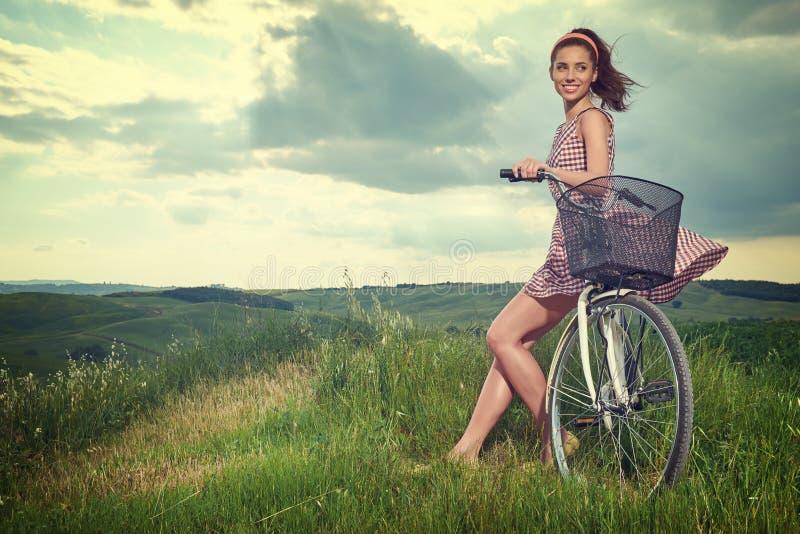 Όμορφη εκλεκτής ποιότητας συνεδρίαση κοριτσιών δίπλα στο ποδήλατο, θερινός χρόνος στοκ φωτογραφίες