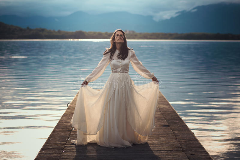 Όμορφη εκλεκτής ποιότητας νύφη σε μια αποβάθρα λιμνών στοκ εικόνες