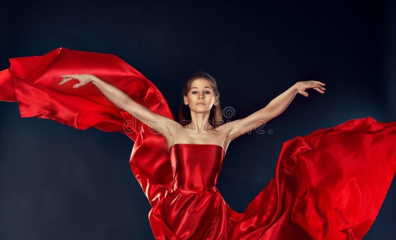 Όμορφη εμπνευσμένη γυναίκα που χορεύει σε ένα κόκκινο πέταγμα φορεμάτων μεταξιού στοκ εικόνα