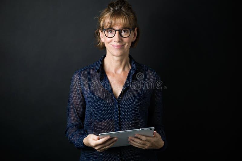 Όμορφη ενήλικη γυναίκα με eyeglasses που εξετάζει τη κάμερα κρατώντας την ψηφιακή ταμπλέτα πέρα από το μαύρο υπόβαθρο στοκ εικόνες