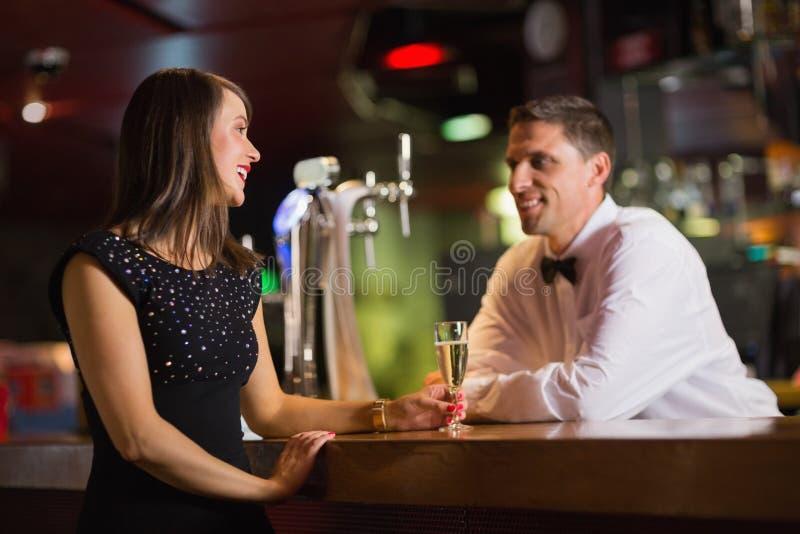 Όμορφη εξυπηρετώντας σαμπάνια μπάρμαν στον πελάτη στοκ φωτογραφία