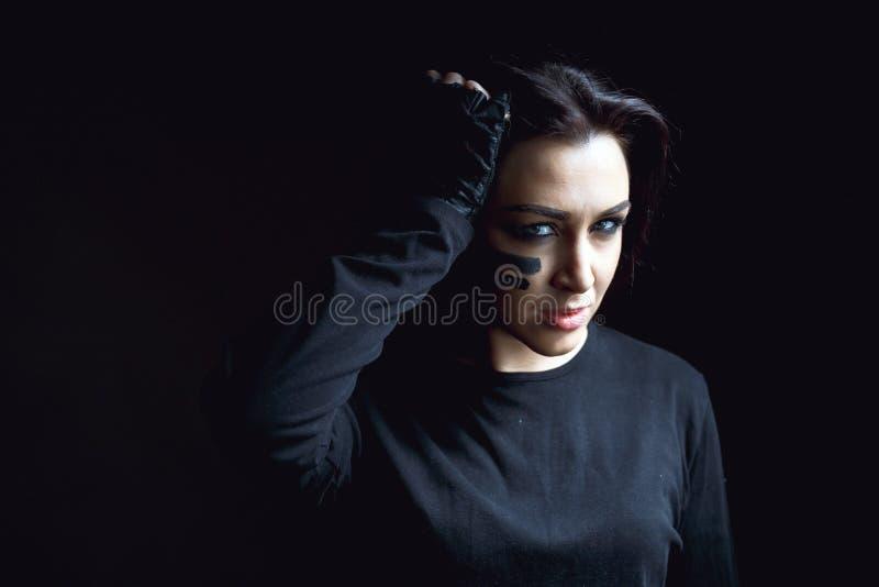Όμορφη επιθετική γυναίκα πέρα από το σκοτεινό υπόβαθρο Σκοτεινές και μυστήριες στάσεις όμορφες κοριτσιών στη σκιά με το χρώμα cam στοκ εικόνα με δικαίωμα ελεύθερης χρήσης