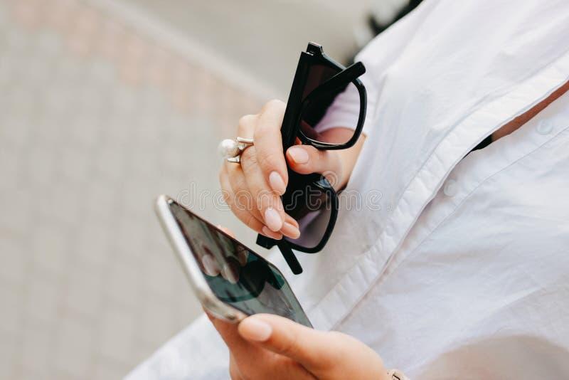 Όμορφη επιτυχής κομψή νέα γυναίκα με τα γυαλιά ηλίου και το κινητό τηλέφωνο στα χέρια της, ύφος οδών, διάστημα αντιγράφων στοκ φωτογραφίες