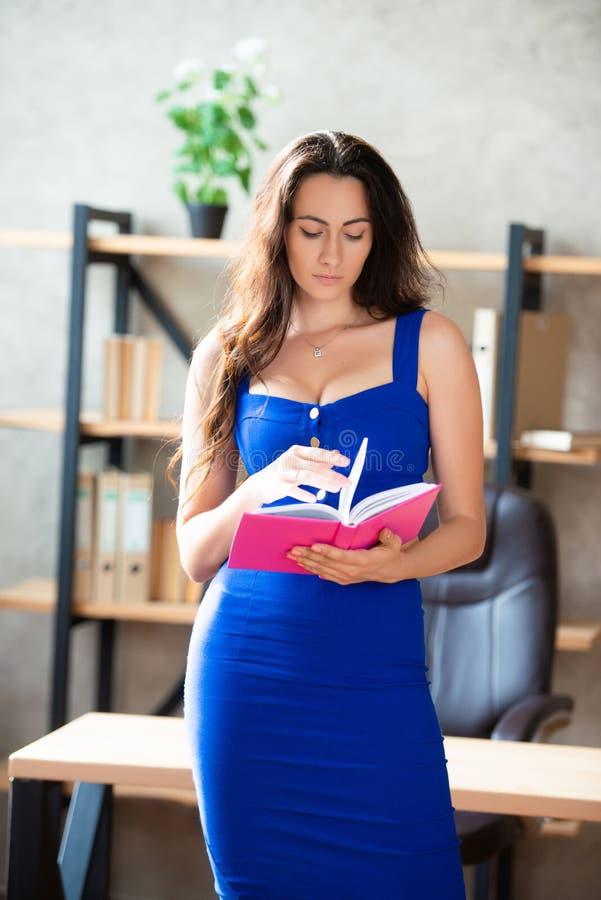 Όμορφη επιχειρηματίας με μπλε φόρεμα στο γραφείο με ένα σημειωματάριο  στοκ εικόνες