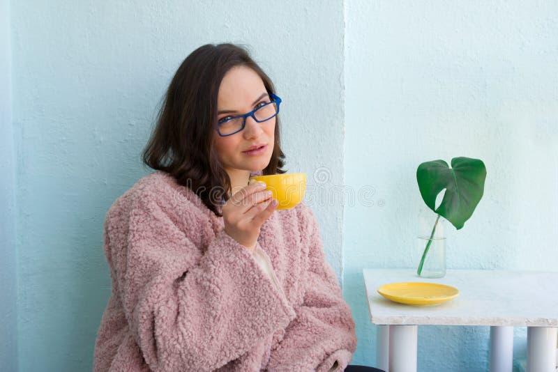 όμορφη επιχειρηματίας στο ρόδινο παλτό γουνών και γυαλιά που κρατούν το κίτρινο φλυτζάνι καφέ στον καφέ κατά τη διάρκεια του μεση στοκ εικόνα με δικαίωμα ελεύθερης χρήσης