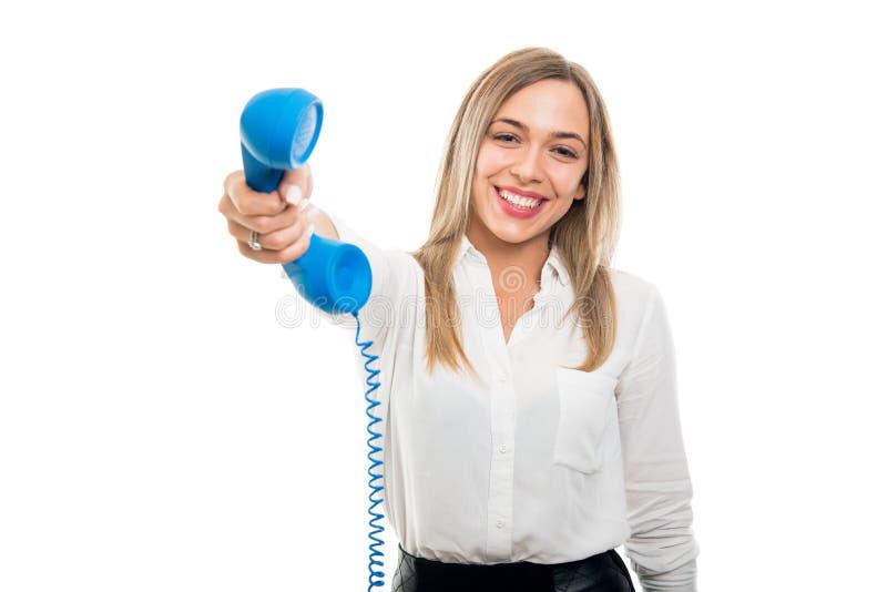 Όμορφη επιχειρησιακή γυναίκα που δίνει το μπλε ακουστικό τηλεφώνου και το χαμόγελο στοκ εικόνα