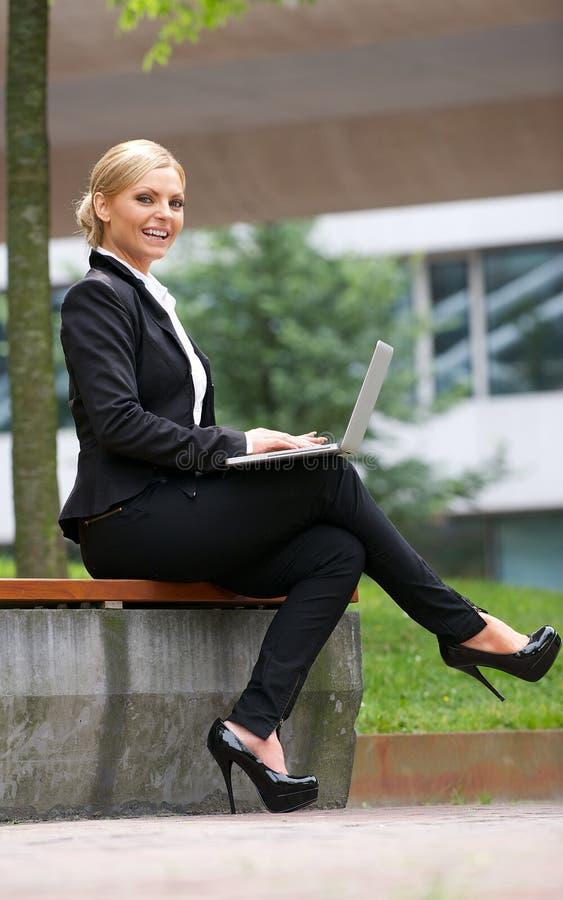 Όμορφη επιχειρησιακή γυναίκα που εργάζεται με το lap-top στο πάρκο στοκ φωτογραφία με δικαίωμα ελεύθερης χρήσης