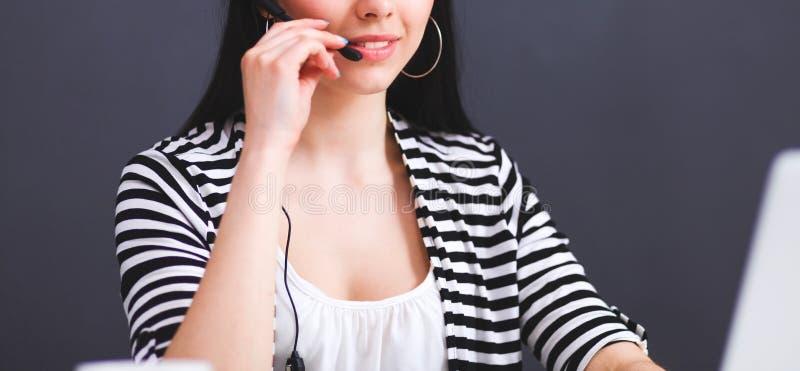 Όμορφη επιχειρησιακή γυναίκα που εργάζεται στο γραφείο της με την κάσκα και το lap-top στοκ εικόνα με δικαίωμα ελεύθερης χρήσης