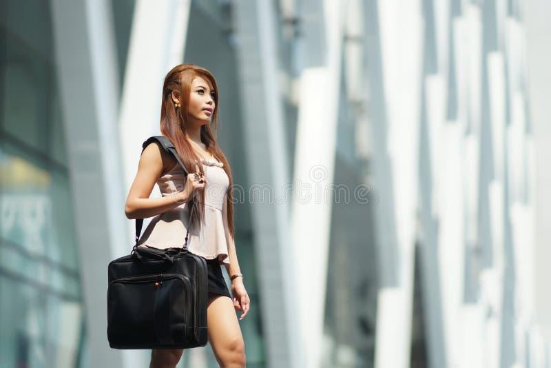 Όμορφη επιχειρησιακή γυναίκα που περπατά έξω από το γραφείο της με το χαρτοφύλακα στοκ εικόνες