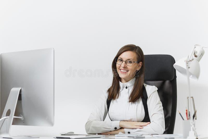 Όμορφη επιχειρησιακή γυναίκα στο κοστούμι και γυαλιά που λειτουργούν στον υπολογιστή με τα έγγραφα στο ελαφρύ γραφείο στοκ φωτογραφίες