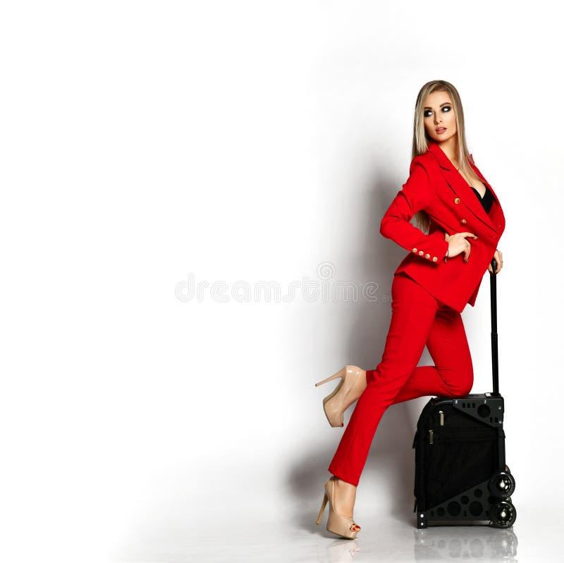 Όμορφη επιχειρησιακή γυναίκα στο πλήρες σώμα βαλιτσών ταξιδιού του κόκκινου περιστασιακού καλλιτέχνη κοστουμιών makeup στοκ εικόνα