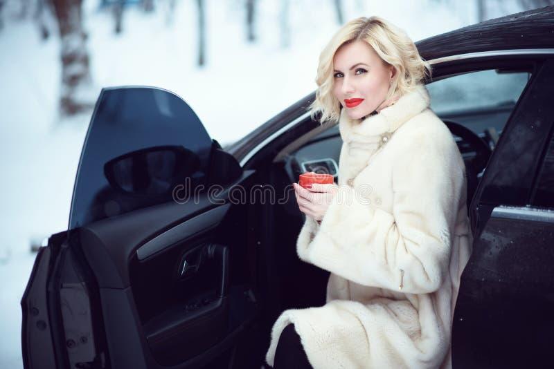 Όμορφη επιχειρησιακή γυναίκα στο πολυτελές άσπρο παλτό γουνών που πίνει τον καυτό καφέ στη χιονώδη συνεδρίαση χειμερινής ημέρας σ στοκ φωτογραφίες με δικαίωμα ελεύθερης χρήσης