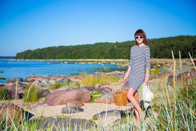 Όμορφη λεπτή γυναίκα που περπατά στην παραλία με το καλάθι πικ-νίκ στοκ εικόνες