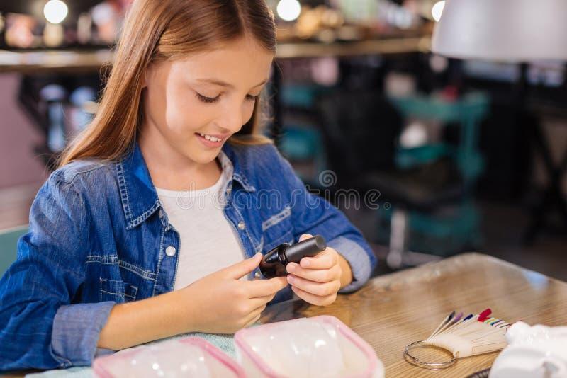 Όμορφη ετικέτα ανάγνωσης κοριτσιών σε ένα μπουκάλι στιλβωτικής ουσίας καρφιών στοκ εικόνες