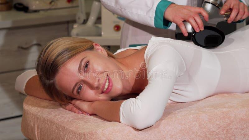 Όμορφη ευτυχής γυναίκα που απολαμβάνει το μασάζ LPG στο σαλόνι ομορφιάς στοκ εικόνες