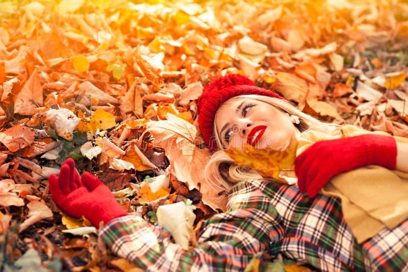 Όμορφη ευτυχής γυναίκα που βρίσκεται στα φύλλα φθινοπώρου στοκ εικόνες