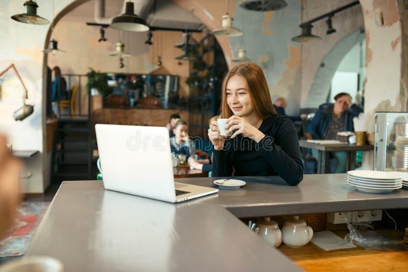 Όμορφη ευτυχής γυναίκα που εργάζεται στο φορητό προσωπικό υπολογιστή κατά τη διάρκεια του διαλείμματος στο φραγμό καφέδων στοκ εικόνα