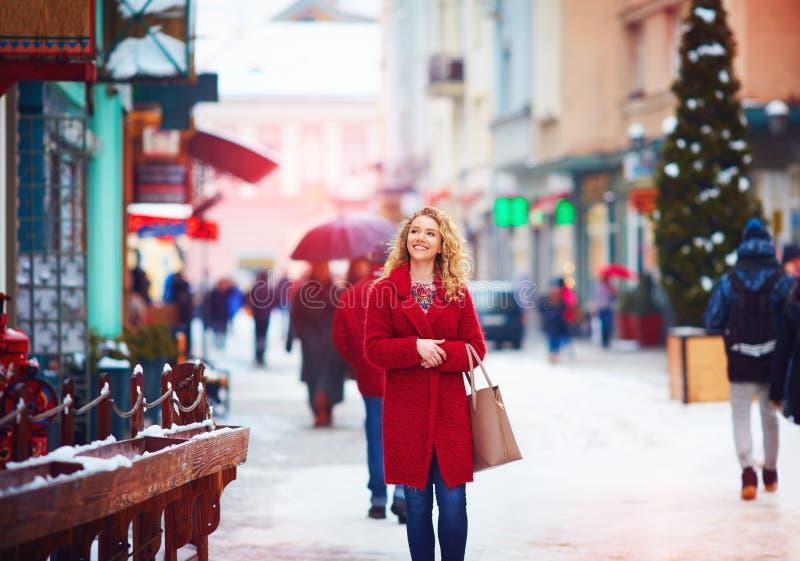 Όμορφη ευτυχής γυναίκα που περπατά στη συσσωρευμένη οδό πόλεων το χειμώνα στοκ εικόνες