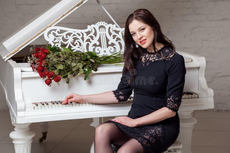 Όμορφη ευτυχής γυναίκα brunette στο μαύρο κλασικό φόρεμα με την ανθοδέσμη των κόκκινων τριαντάφυλλων που κάθονται στο πιάνο και π στοκ εικόνα