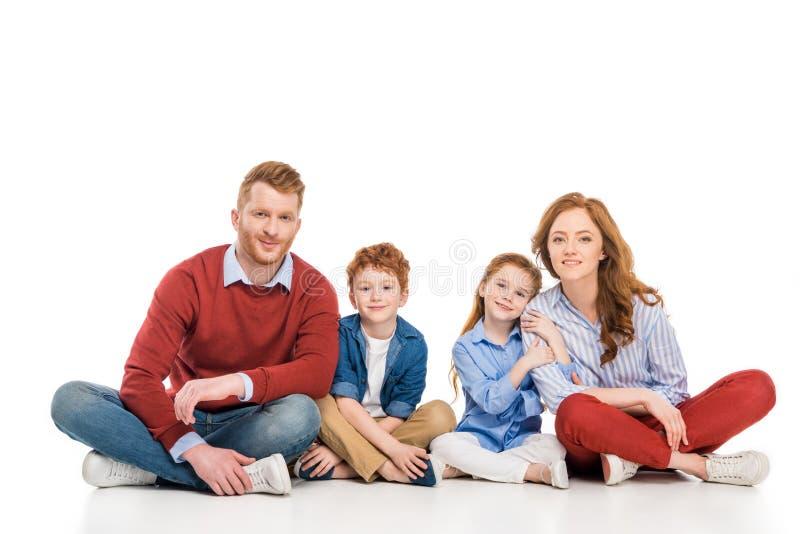 όμορφη ευτυχής κοκκινομάλλης οικογένεια με δύο παιδιά που κάθονται μαζί και που χαμογελούν στη κάμερα στοκ φωτογραφίες με δικαίωμα ελεύθερης χρήσης