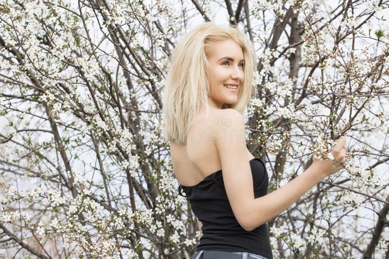 Όμορφη ευτυχής νέα γυναίκα που απολαμβάνει τη μυρωδιά σε έναν ανθίζοντας κήπο άνοιξη στοκ φωτογραφία με δικαίωμα ελεύθερης χρήσης