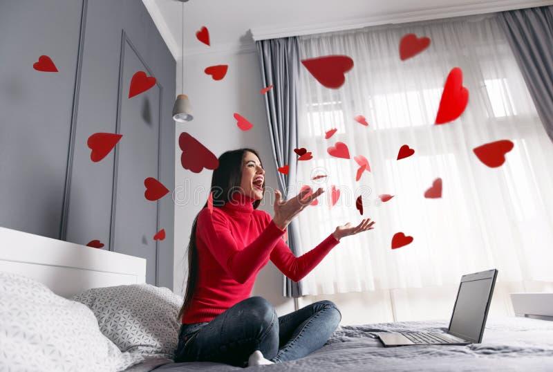 Όμορφη, ευτυχής, νέα γυναίκα που ρίχνει τις κόκκινες καρδιά-μορφές στον αέρα στοκ φωτογραφία με δικαίωμα ελεύθερης χρήσης