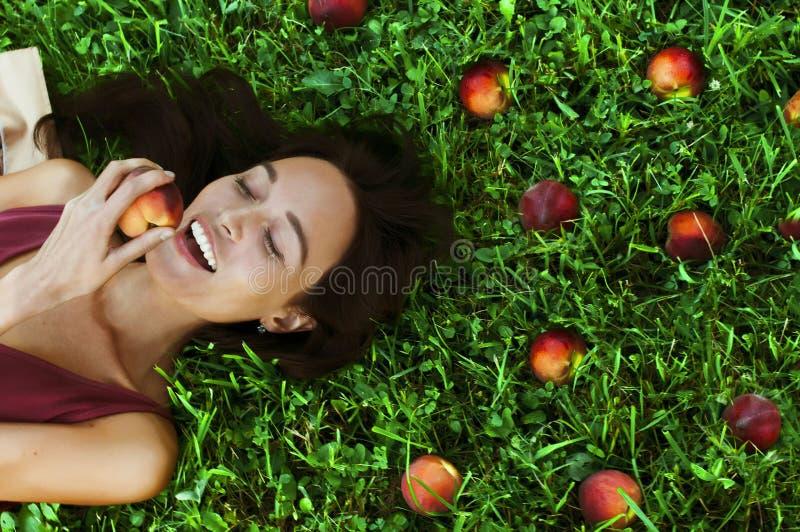 Όμορφη ευτυχής νέα γυναίκα που χαμογελά τρώγοντας ένα ροδάκινο στοκ εικόνες