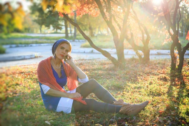 Όμορφη ευτυχής νέα γυναίκα στο πάρκο φθινοπώρου Η χαρούμενη γυναίκα μιλά σε ένα έξυπνο τηλέφωνο υπαίθρια σε ένα ανοιχτό κίτρινο στοκ εικόνα
