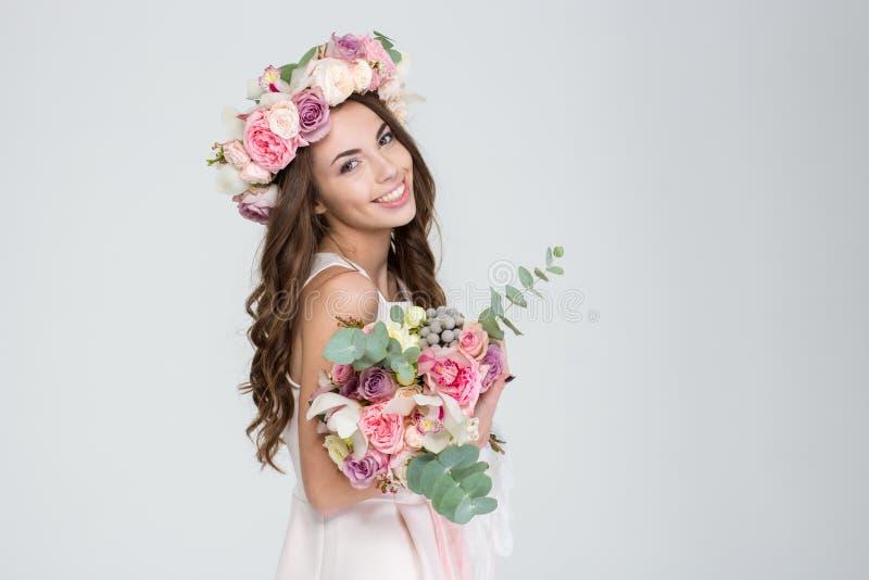 Όμορφη ευτυχής νύφη στη ροδαλή ανθοδέσμη εκμετάλλευσης στεφανιών των λουλουδιών στοκ φωτογραφίες με δικαίωμα ελεύθερης χρήσης