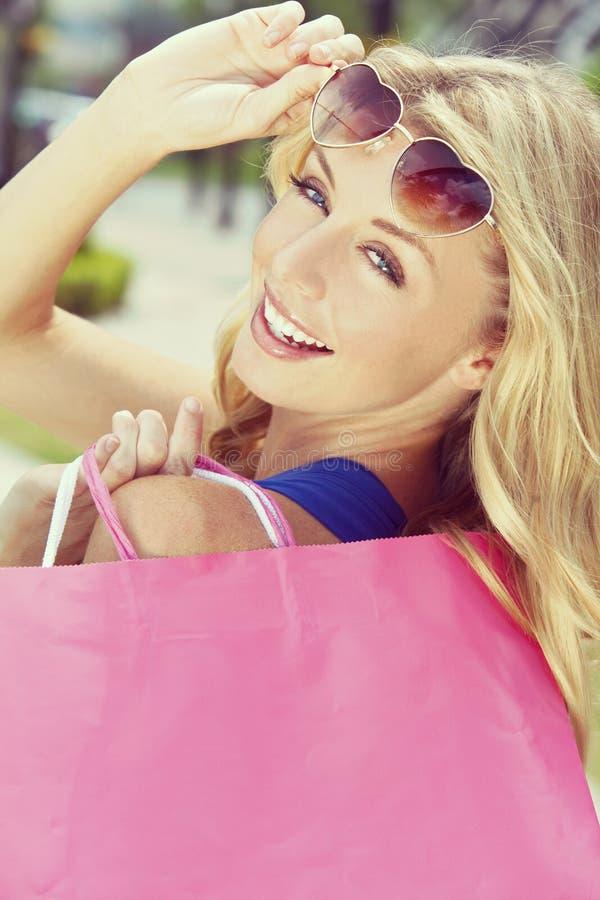Όμορφη ευτυχής ξανθή γυναίκα με τις τσάντες αγορών στοκ εικόνα