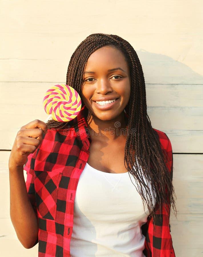 Όμορφη ευτυχής χαμογελώντας αφρικανική γυναίκα πορτρέτου με το γλυκό lollipop στοκ φωτογραφία