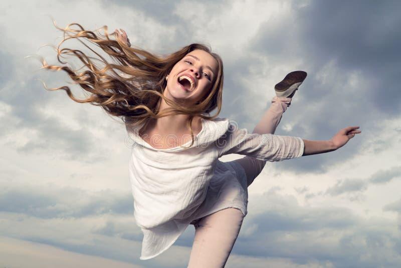 Όμορφη ευτυχής χαμογελώντας γυναίκα με την τρίχα που πετά στο υπόβαθρο ουρανού στοκ φωτογραφία με δικαίωμα ελεύθερης χρήσης