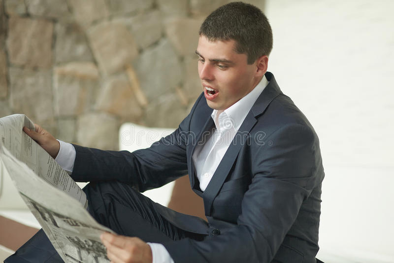 Όμορφη εφημερίδα πρωινού ανάγνωσης νεαρών άνδρων στο μαύρο κοστούμι στοκ εικόνες