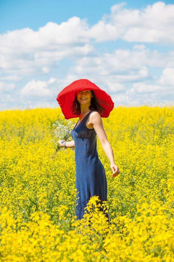 Όμορφη εύθυμη γυναίκα σε ένα κόκκινο καπέλο με μια ανθοδέσμη στα χέρια στοκ εικόνες