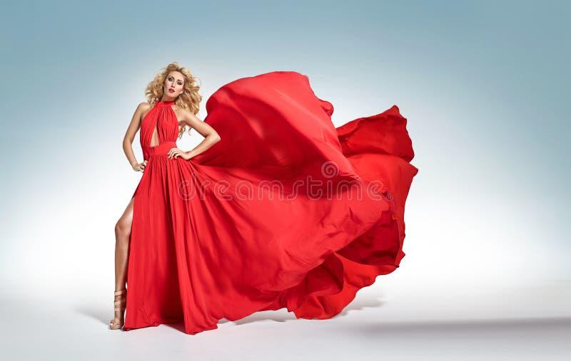 Όμορφη δελεαστική ξανθή γυναίκα στο κόκκινο κυματίζοντας φόρεμα στοκ εικόνες