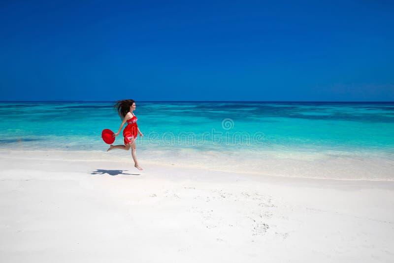 Όμορφη ελεύθερη νέα γυναίκα που πηδά στην εξωτική θάλασσα, ευτυχές brun στοκ φωτογραφίες