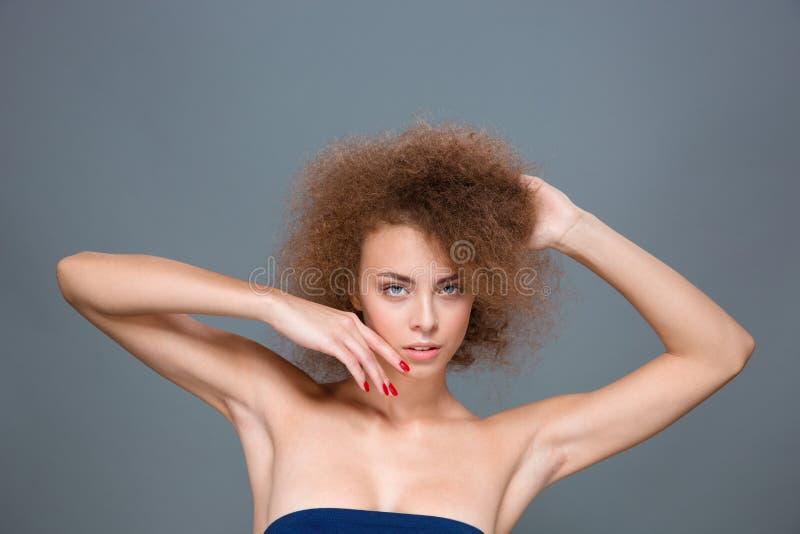 Όμορφη ελκυστική βέβαια τοποθέτηση γυναικών στο γκρίζο υπόβαθρο στοκ εικόνα