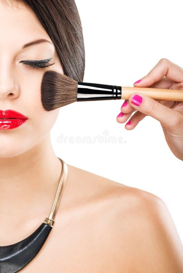 Όμορφη ελκυστική γυναίκα με το μισό πρόσωπο, βούρτσα πολυτέλειας makeup του προσώπου του στοκ εικόνα