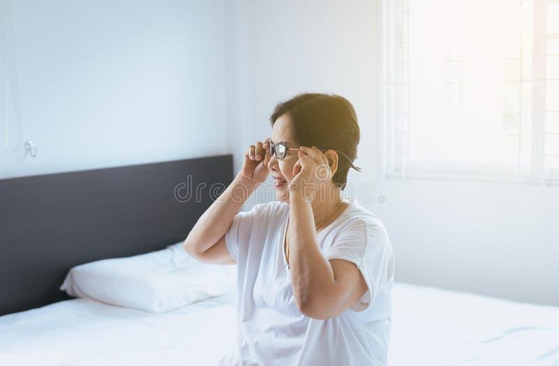 Όμορφη ηλικιωμένη γυναίκα χρησιμοποιώντας eyeglass και χαμογελώντας καθμένος στην κρεβατοκάμαρα στο σπίτι στοκ εικόνες