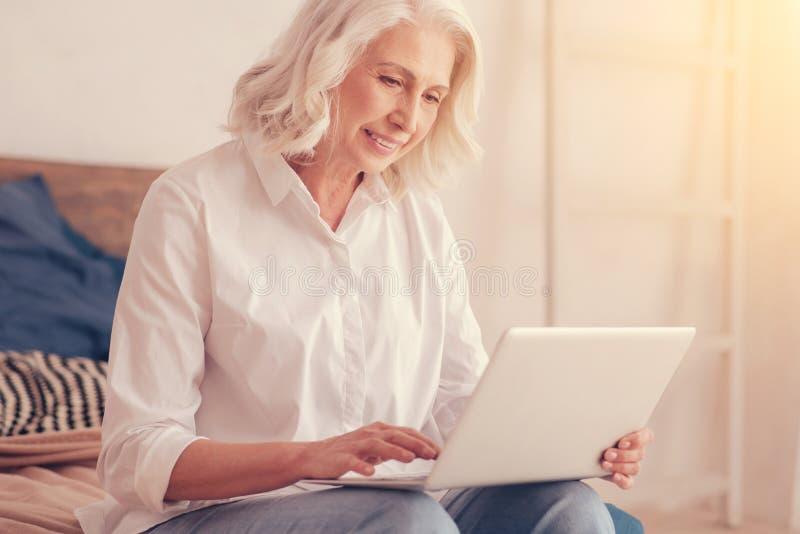 Όμορφη ηλικιωμένη κυρία που εργάζεται στο lap-top στο σπίτι στοκ φωτογραφίες